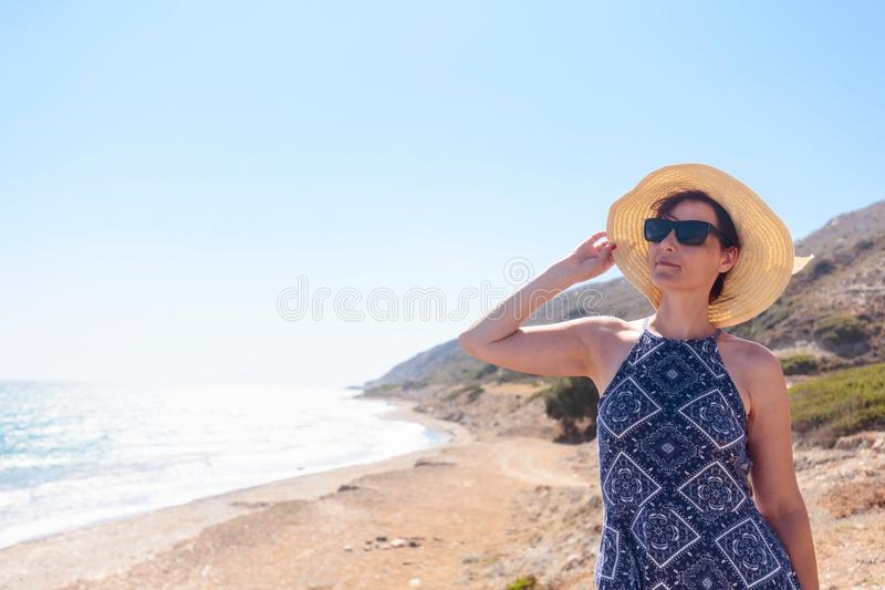 Middle-aged woman with sunglasses and a hat on the Mediterranean royalty free stock photography