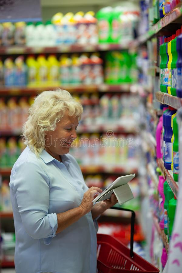 A middle aged woman with a tablet in a household section of a supermarket. A middle aged fair haired woman is standing in a household section of a supermarket royalty free stock photo