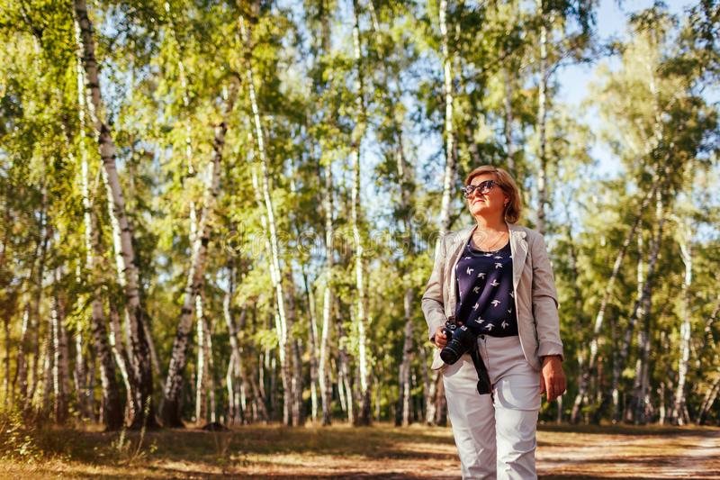 Middle-aged woman taking pictures using camera in autumn forest. Senior woman walking and enjoying hobby royalty free stock photo