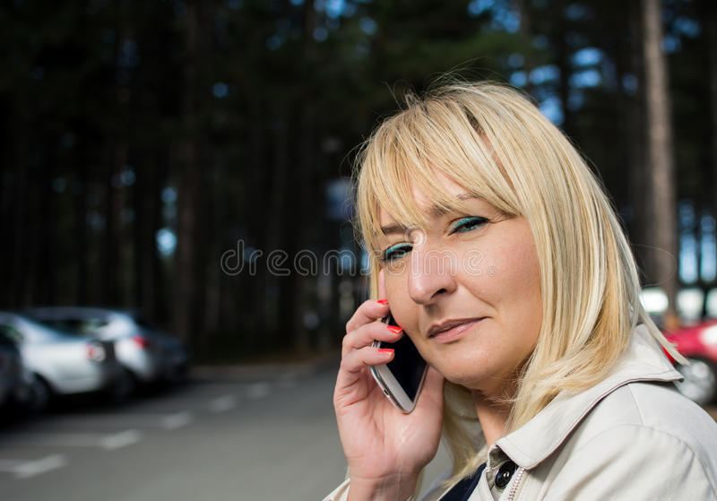 Middle aged woman talking on mobile. Blond hair. Smiling. stock photography