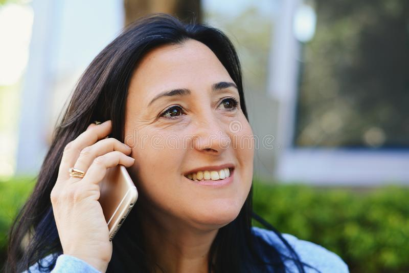 Middle aged woman talking on phone royalty free stock photos