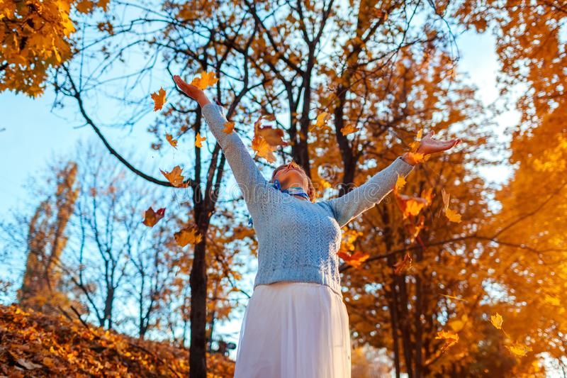 Middle-aged woman throwing leaves in autumn forest. Senior woman having fun outdoors. Middle-aged woman throwing leaves in autumn forest at sunset. Senior woman stock image