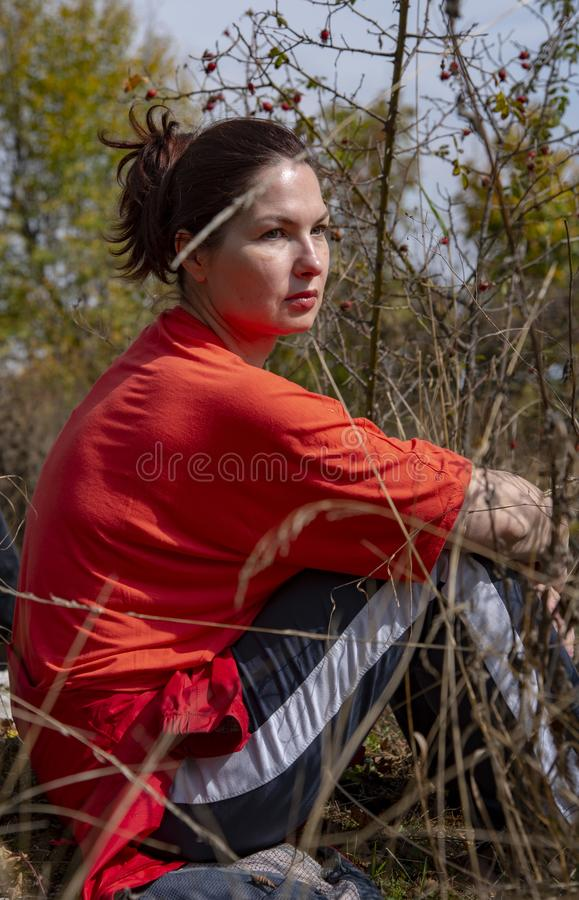 A middle-aged woman in a tracksuit sits on the ground. In the sunlight stock photos
