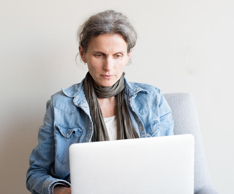Middle aged woman using computer. Middle aged woman with grey hair and denim shirt and scarf seated using computer royalty free stock image