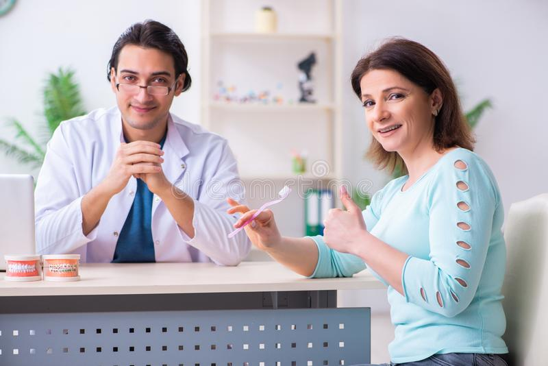 Middle-aged woman visiting male doctor stomatologist. The middle-aged women visiting male doctor stomatologist stock images