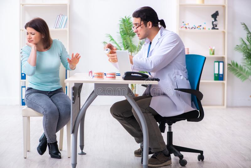 Middle-aged woman visiting male doctor stomatologist. The middle-aged women visiting male doctor stomatologist stock photos