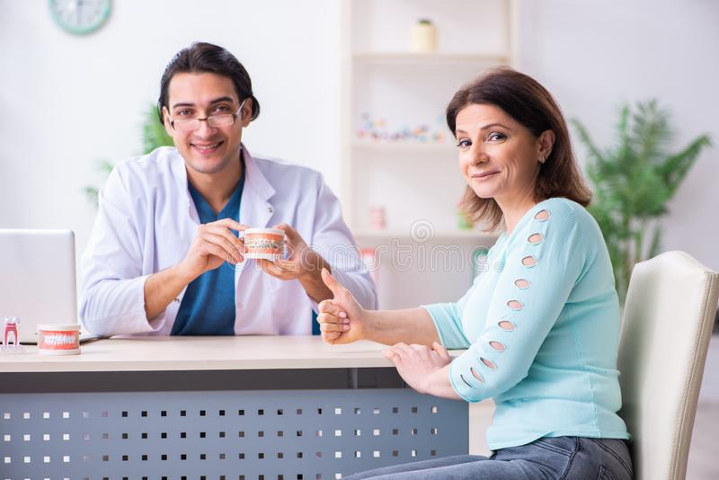 Middle-aged woman visiting male doctor stomatologist. The middle-aged women visiting male doctor stomatologist royalty free stock photos