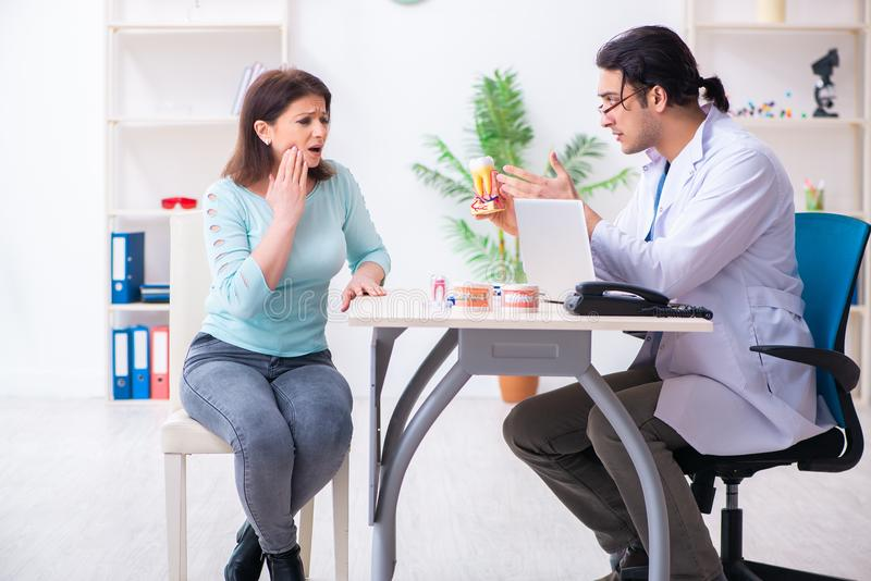 Middle-aged woman visiting male doctor stomatologist. The middle-aged women visiting male doctor stomatologist royalty free stock images