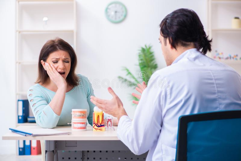 Middle-aged woman visiting male doctor stomatologist. The middle-aged women visiting male doctor stomatologist royalty free stock image