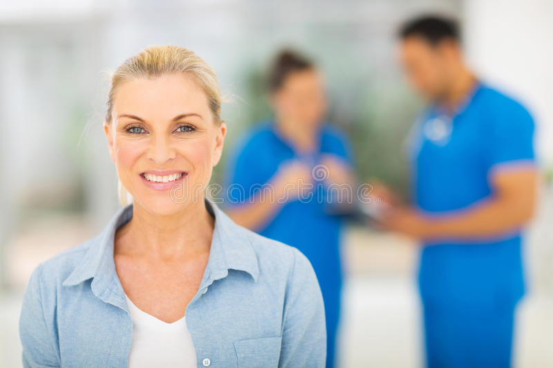 Middle aged woman waiting for checkup in doctor's office. Smiling middle aged woman waiting for checkup in doctor's office royalty free stock images