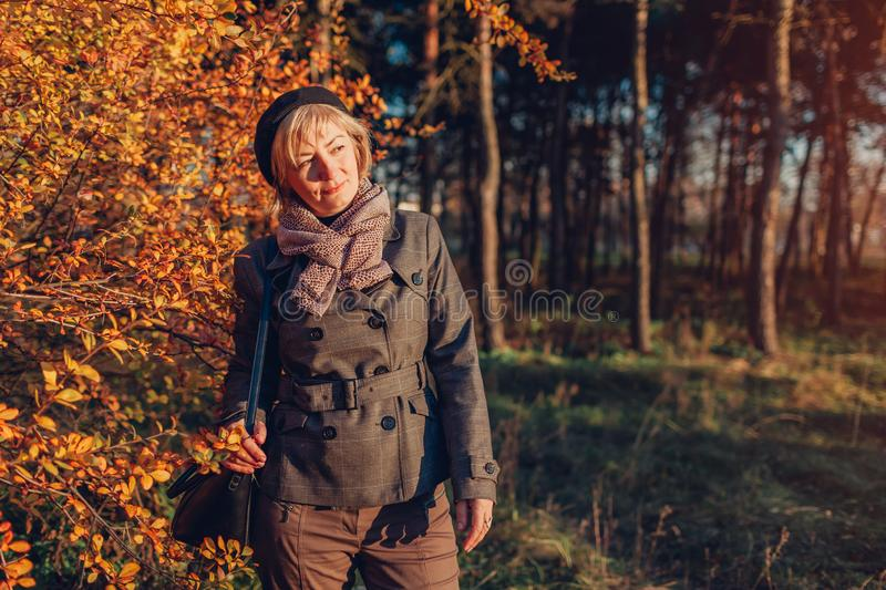 Middle-aged woman walking in autumn forest. Senior lady wearing stylish fall outfit with accessories. Outdoors stock photo