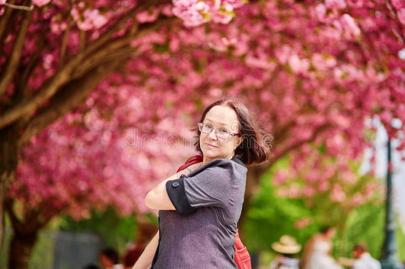 Middle aged woman walking in Paris on a spring day. With cherry blossoms in full bloom royalty free stock photos