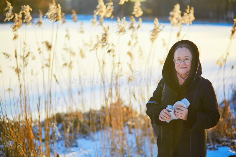 Middle aged woman walking in park on a winter day. Beautiful middle aged woman walking in park on a winter day stock photography