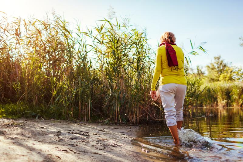 Middle-aged woman walking on river bank on autumn day. Senior lady having fun in the forest enjoying nature royalty free stock photos