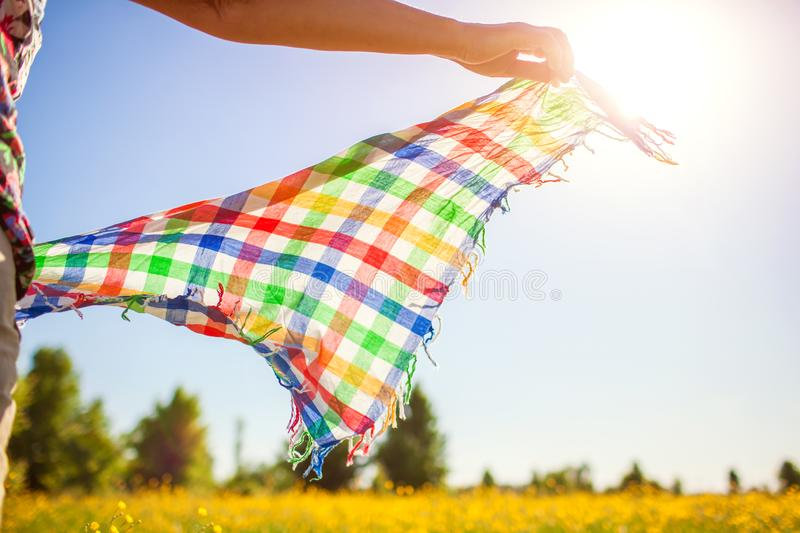 Middle-aged woman walking in spring field at sunset among flowers and holding scarf shaking on wind stock photos
