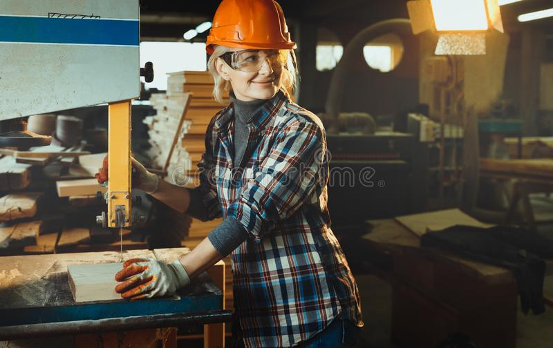 Middle aged woman working with a drill in workshop with copy cpace. Concept of woman in a male-dominated profession, stock image