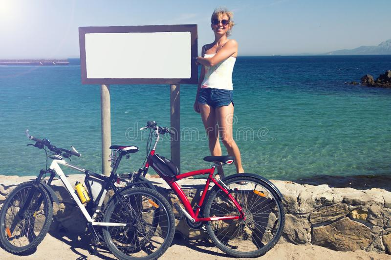 Middle aged women girl stays with two bicycles at seaside coastl royalty free stock photography