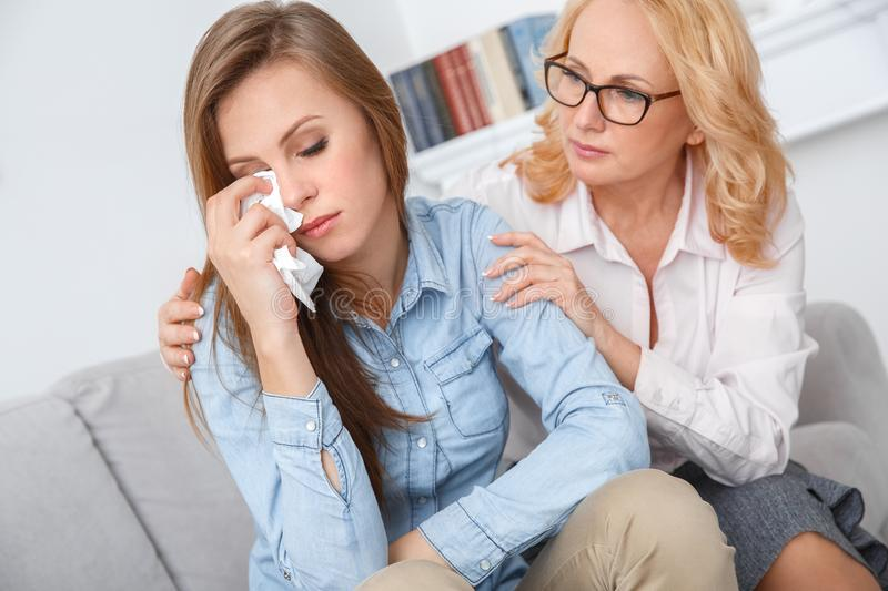 Female psychologyst therapy session with client indoors sitting patient wiping tears away stock photography