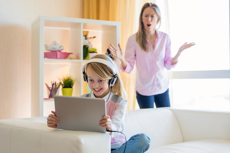 Woman is scolding her teenage daughter, girl is listening to music in headphones and ignoring her mom royalty free stock photography