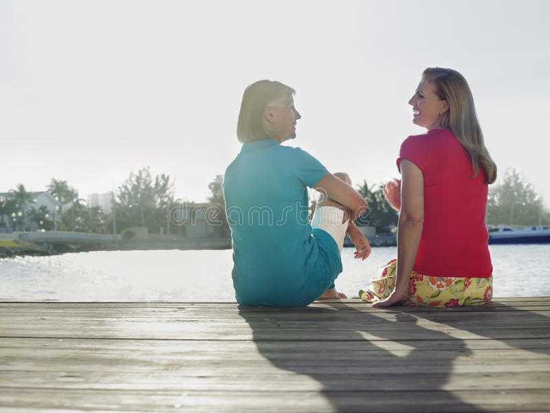Middle Aged Women Sitting On Pier stock images