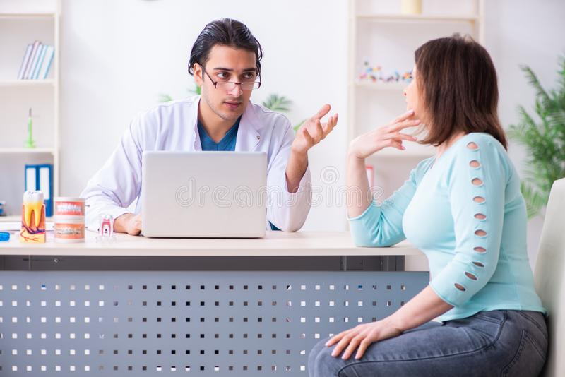 Middle-aged woman visiting male doctor stomatologist. The middle-aged women visiting male doctor stomatologist royalty free stock photography