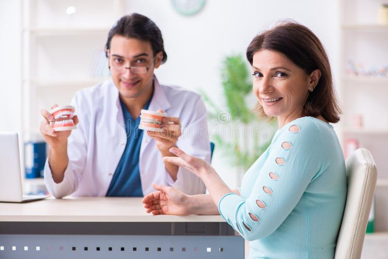 Middle-aged woman visiting male doctor stomatologist royalty free stock photos