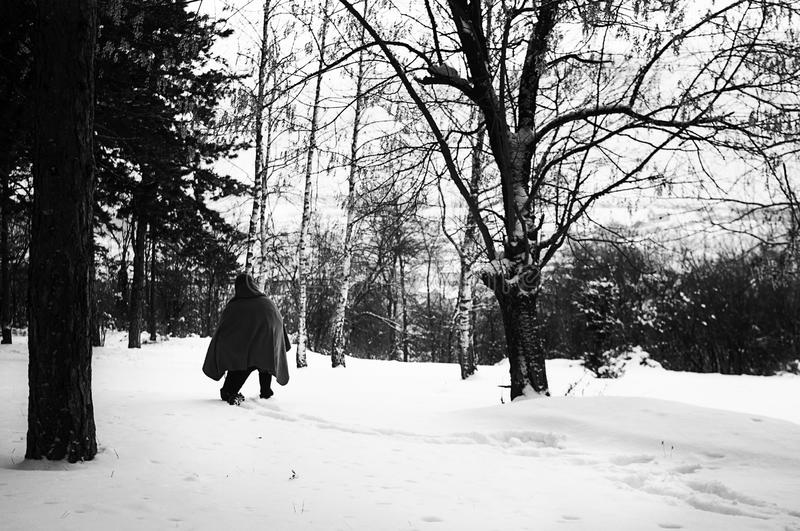 Middle East or African refugee is walking through snowy forest on the Balkan route royalty free stock image