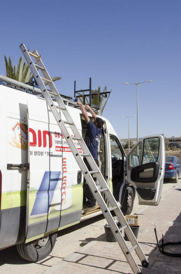 Middle East- Mitzpe Ramon, Israel. February 29, A worker with a ladder and car stock photo