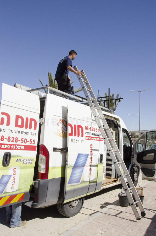 Middle East- Mitzpe Ramon, Israel. February 29, A worker with a ladder on the roof of the car stock photos