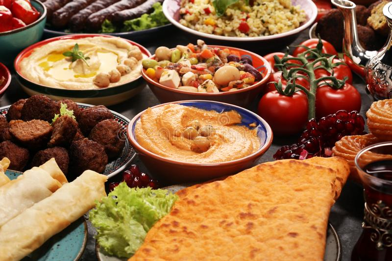 Middle eastern or arabic dishes and assorted meze, concrete rustic background. Falafel. Turkish Dessert Baklava with pistachio. Meat kebab, falafel, baba royalty free stock photos