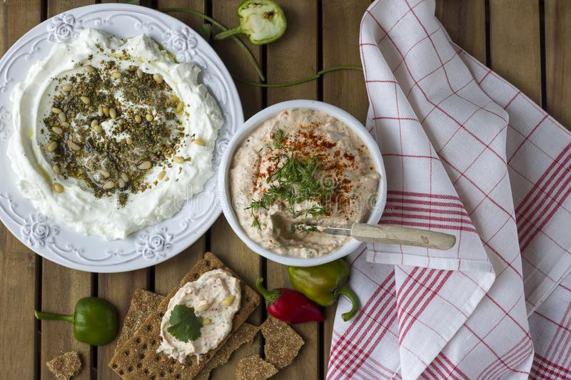Middle Eastern dish - dense homemade labneh yoghurt with zatar in white dishes. Daylight. stock photos