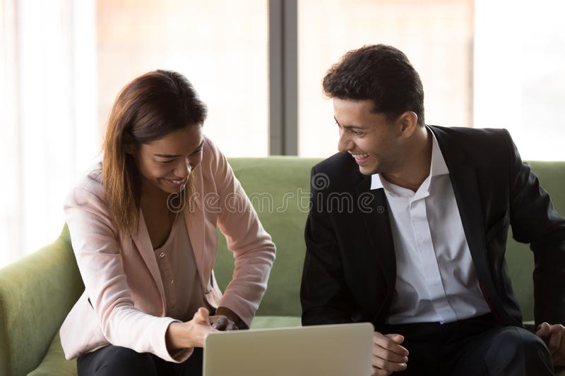 Funny diverse colleagues using laptop sitting on couch at work royalty free stock image