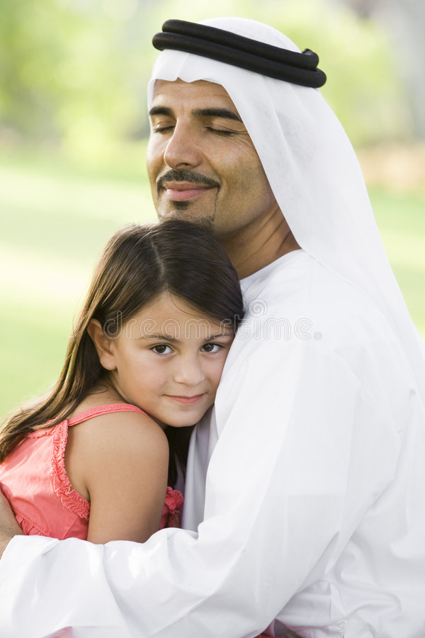 A Middle Eastern man and his daughter in a park