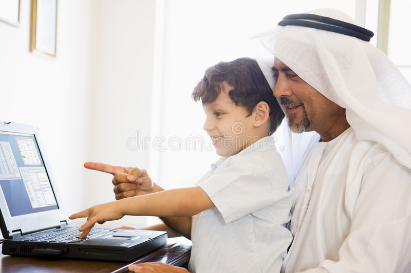 A Middle Eastern man and his son. Sitting in a home office royalty free stock images