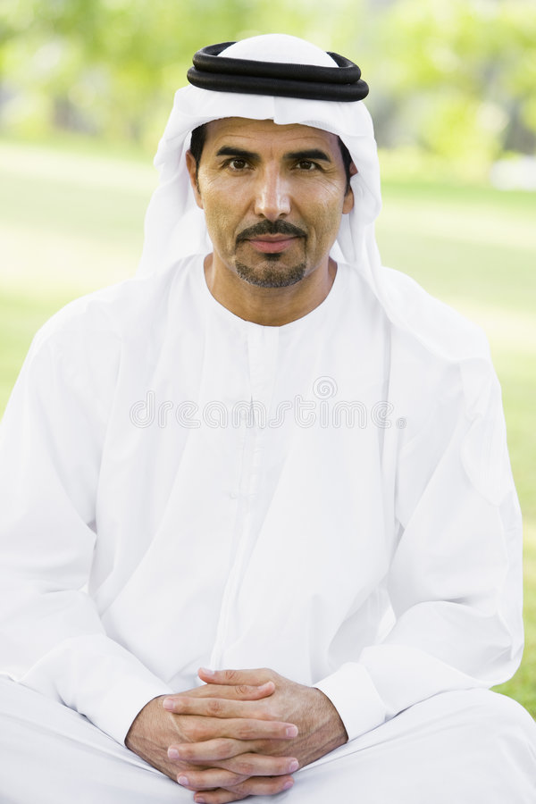 A Middle Eastern man sitting in a park stock photos