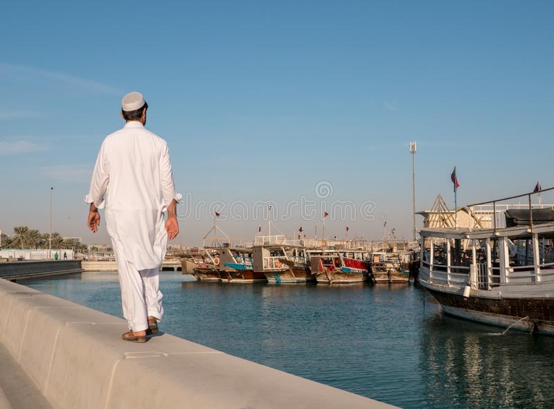 Middle eastern Man Walking by Corniche road in Doha. View with Traditional Wooden Boats with Floating Qatar Flags. Corniche Broadway. Qatar, Middle East royalty free stock photo