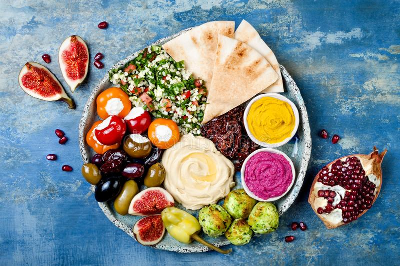 Middle Eastern meze platter with green falafel, pita, sun dried tomatoes, pumpkin, beet hummus, olives, stuffed peppers, tabbouleh stock photo