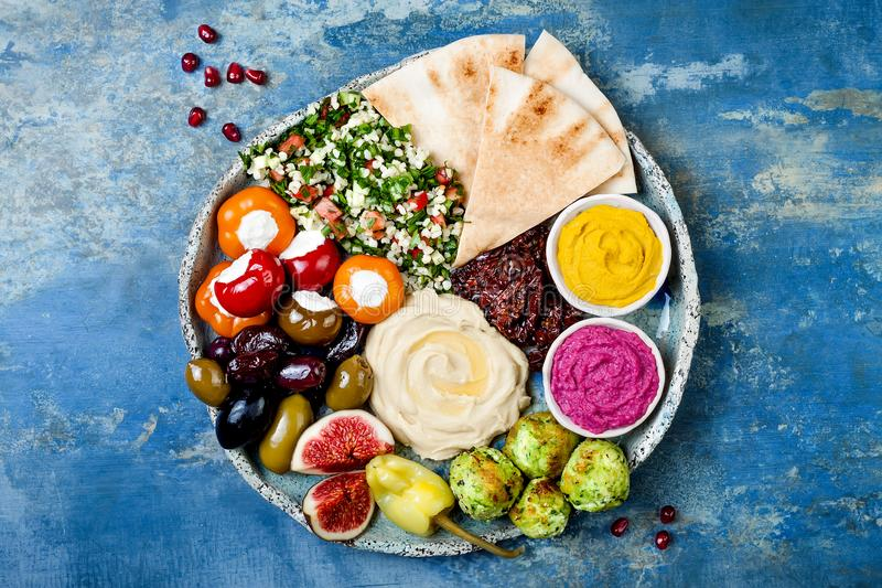 Middle Eastern meze platter with green falafel, pita, sun dried tomatoes, pumpkin, beet hummus, olives, stuffed peppers, tabbouleh stock image