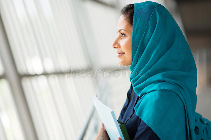 Middle eastern student daydreaming. Side view of a pretty middle eastern college student daydreaming stock photography