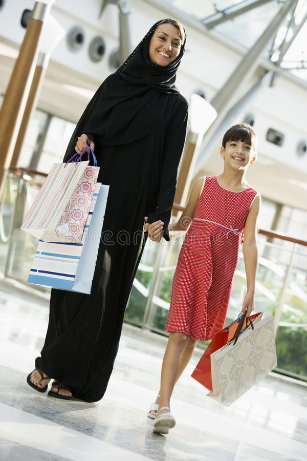 A Middle Eastern woman with a girl shopping royalty free stock image