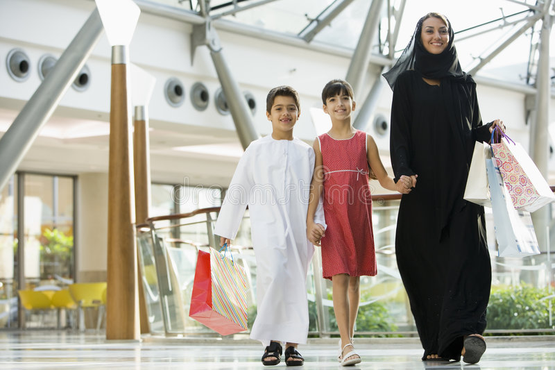 A Middle Eastern woman with two children shopping. A Middle Eastern woman with two children in a shopping mall stock images