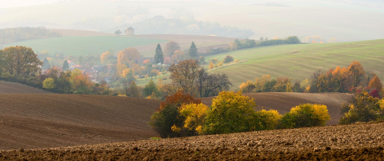 Middle-European Autumn Morning Landscape With Many Interesting Details:Mill In The Haze,Herd Of Grazing Deer, Plowed Brown Fields stock photography