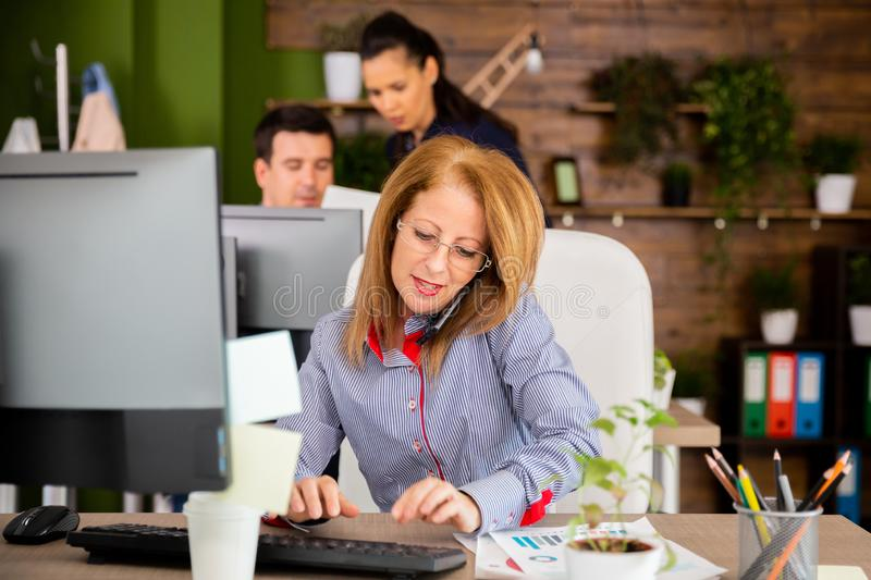 Middle female typing while having a serios conversation on her phone royalty free stock photography