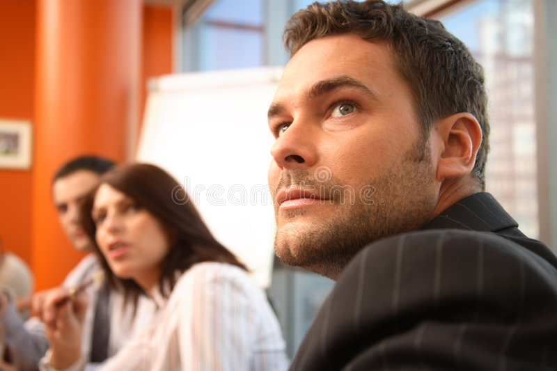 In the middle of meeting. Group of business people at the business meeting -2 men and 1 woman stock image