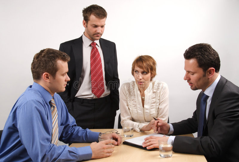 In the middle of meeting. Four businesspeople gathered around a table for a meeting, brainstorming royalty free stock images