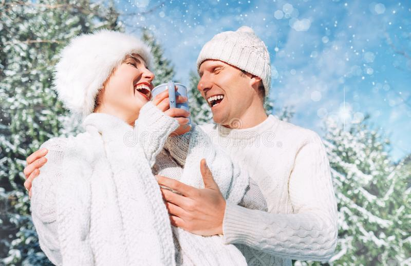 Middle shot of happy cheerful sincerely laughing caucasian couple dressed knitted outfit clothes in the snowy winter forest. stock photo