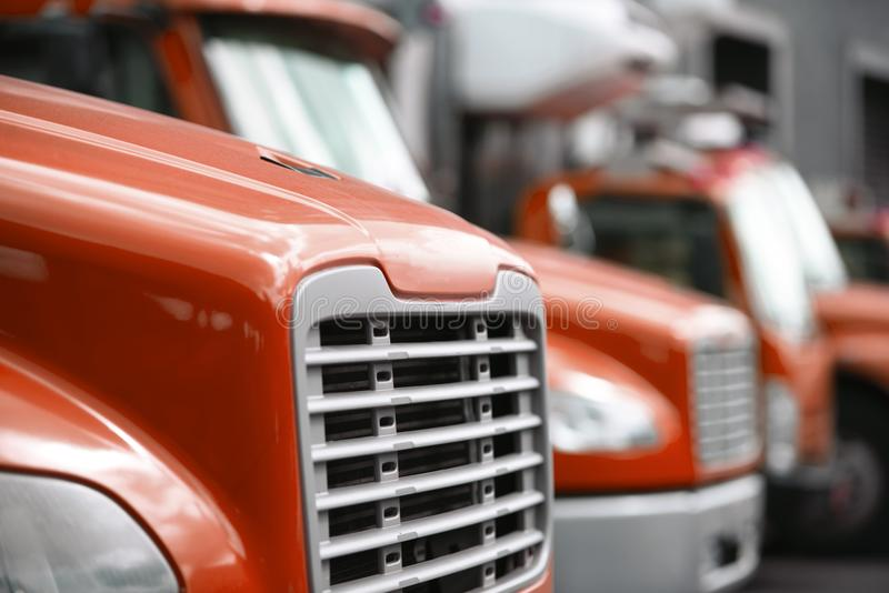 Middle sized rigs semi trucks standing in row in warehouse dock stock photography