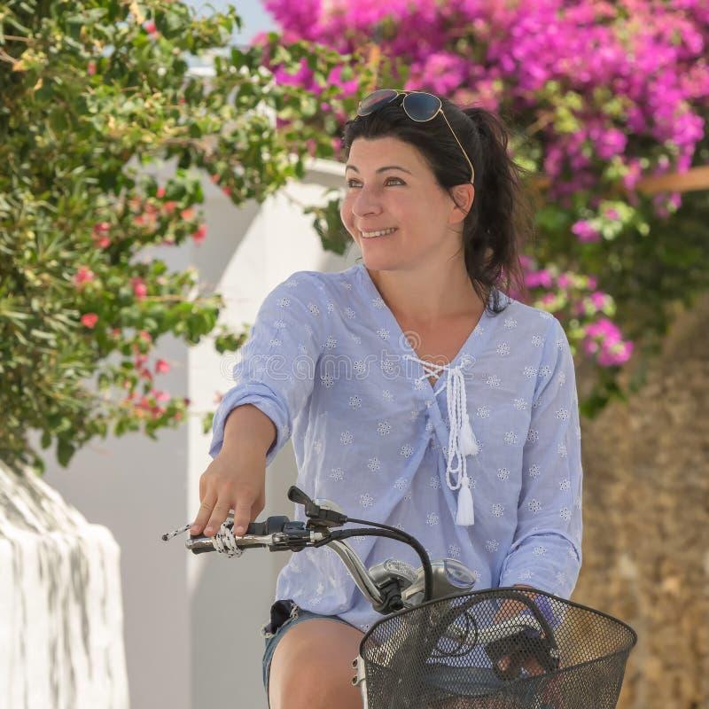 Middled åldrades modellen överst av cykeln mot en härlig bakgrund på den Andros ön i Grekland royaltyfri fotografi