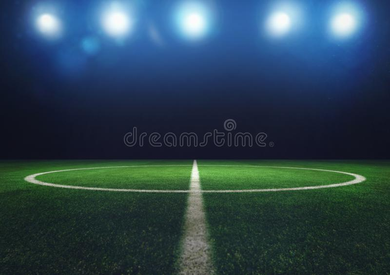 Midfield of grass soccer field at night with headlights royalty free stock images