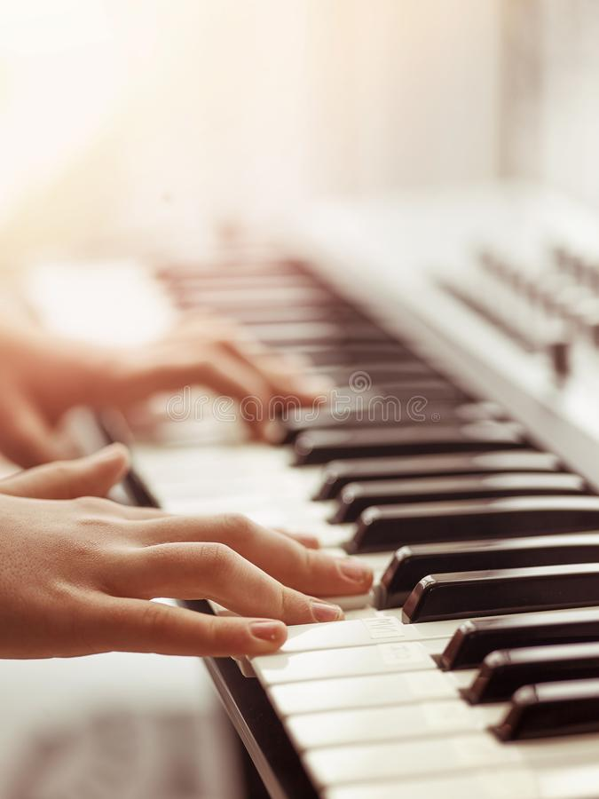 Midi keyboard or electronic piano and playing child hands. royalty free stock photography